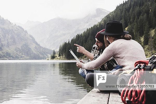 Österreich  Tirol  Alpen  Paar mit Landkarte am Steg am Bergsee