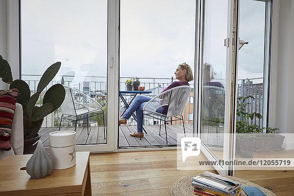 Reife Frau zu Hause auf dem Balkon sitzend
