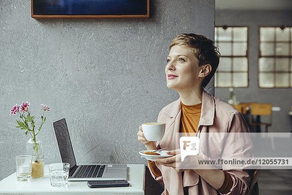 Frau mit ihrem Laptop bei einer Tasse Kaffee im Cafe