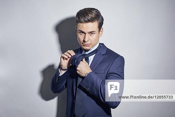 Porträt eines jungen Geschäftsmannes  der seine Krawatte bindet