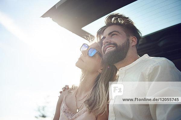 Glückliches junges Paar sitzt im Kofferraum eines offenen Autos