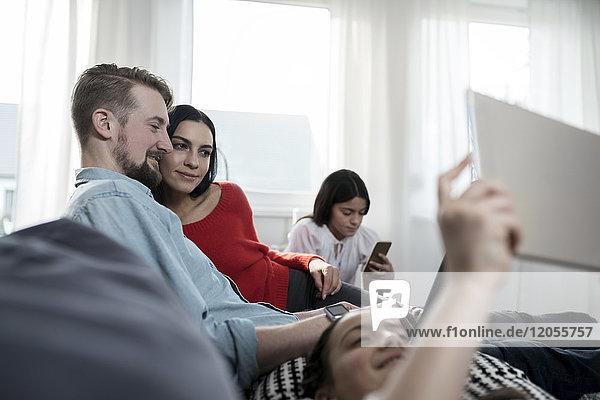 Familie sitzt auf dem Sofa mit zwei Töchtern  die Tablett und Smartphone halten.