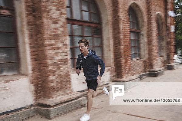 Junger Mann läuft am Backsteingebäude entlang