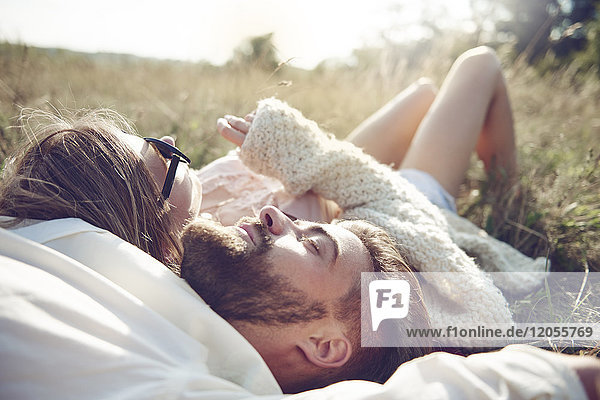 Glückliches junges Paar im Gras liegend