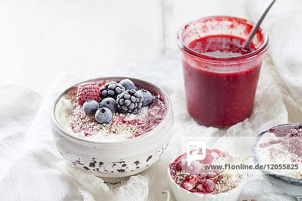 Schale Naturjoghurt mit Himbeersauce und gefrorenen Früchten