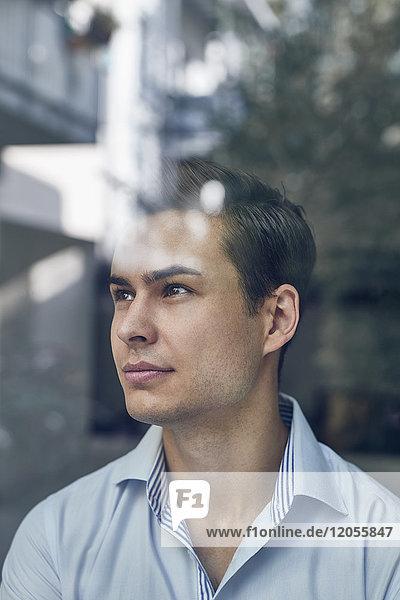 Porträt eines jungen Geschäftsmannes hinter einer Glasscheibe im Büro