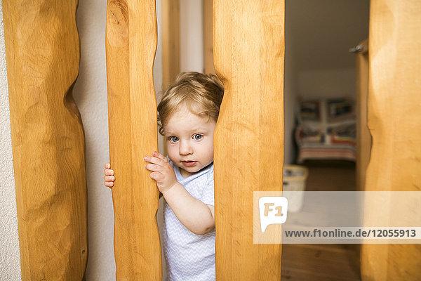 Kleiner Junge hinter einer Holzschranke