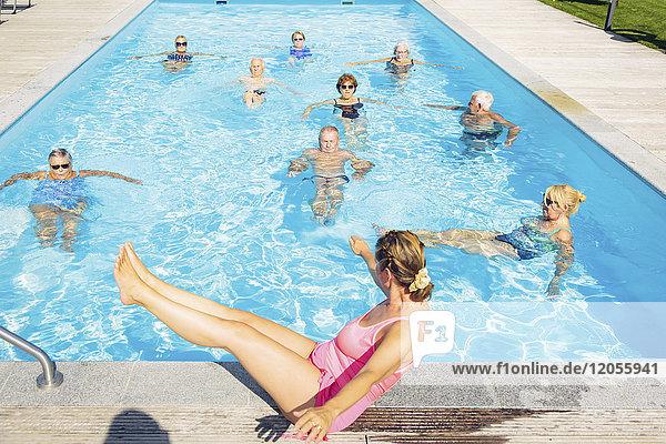 Gruppe von Senioren mit Trainer beim Wassergymnastik im Schwimmbad