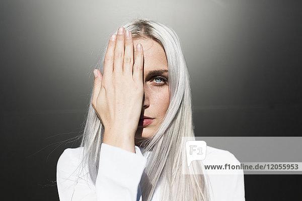 Porträt einer ernsthaften jungen Frau,  die ein Auge bedeckt