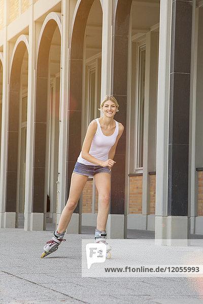 Porträt der lächelnden jungen Frau beim Inline-Skaten