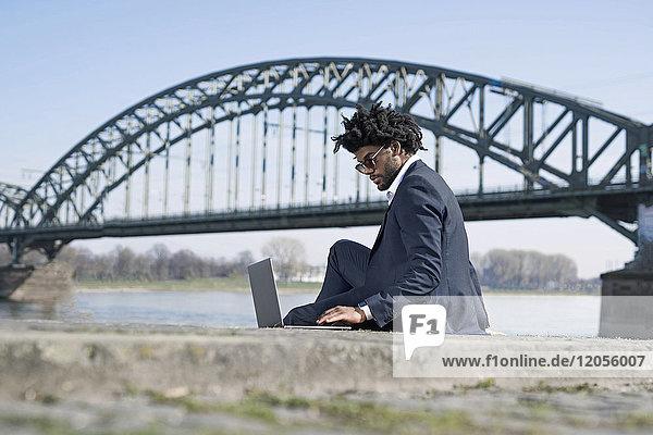 Businessman sitting at the riverside using laptop