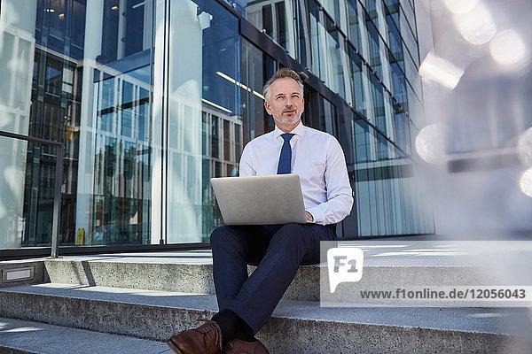 Portrait eines Geschäftsmannes mit Laptop auf einer Treppe sitzend