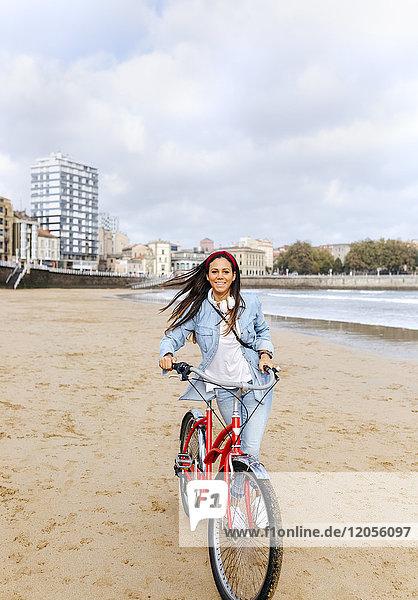 Spanien  Gijon  junge Frau beim Radfahren am Strand