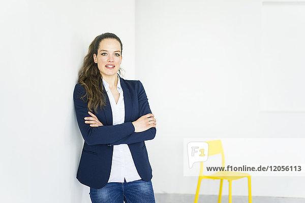 Porträt einer Geschäftsfrau in einem Zimmer mit gelbem Stuhl