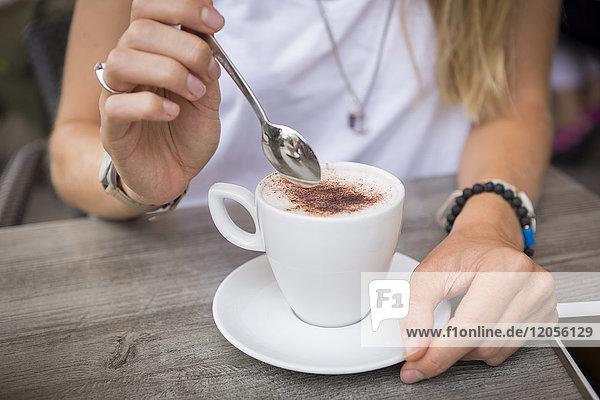 Nahaufnahme einer Frau mit Cappuccino in einem Straßencafé