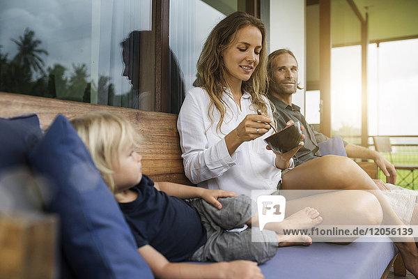 Familie sitzt auf der Bank auf dem Balkon und genießt gemeinsam den Sonnenuntergang.