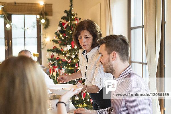 Mutter überreicht Teller am Weihnachtstisch