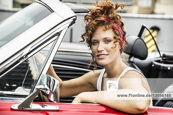 Porträt der lächelnden Rothaarigen im Sportwagen