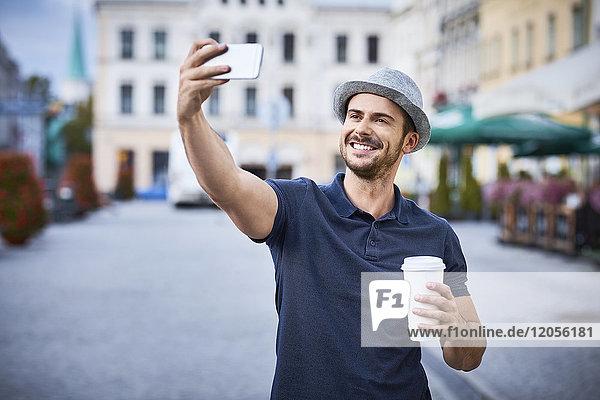 Mann  der Selfie in der Stadt mit Kaffee und Filzhut nimmt