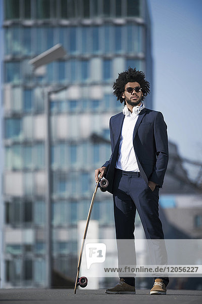 Businessman with longboard standing in front of skyscraper