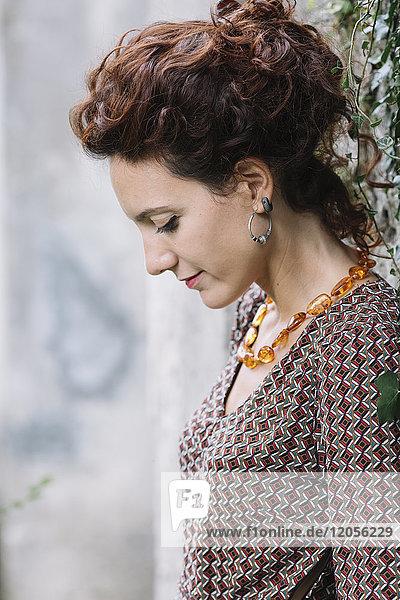 Frau in elegantem Kleid an der Wand lehnend