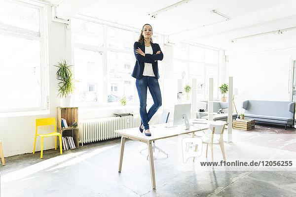 Porträt einer Geschäftsfrau  die auf dem Tisch in einem Loft steht.
