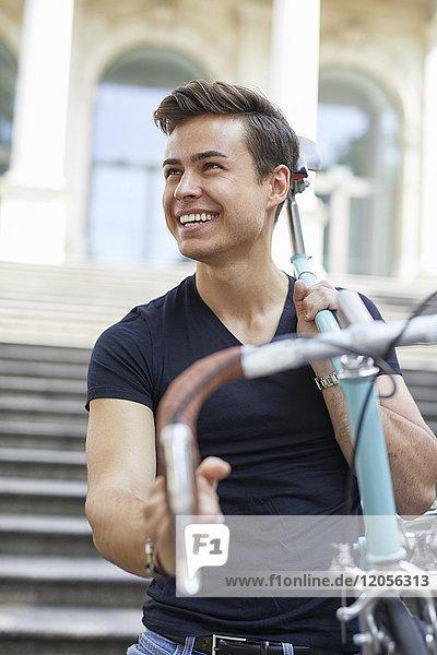 Porträt eines glücklichen jungen Mannes mit Rennrad auf der Schulter