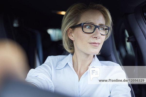 Blonde Geschäftsfrau mit Brille beim Autofahren