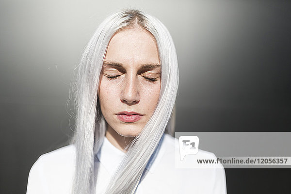 Porträt einer ernsthaften jungen Frau mit geschlossenen Augen