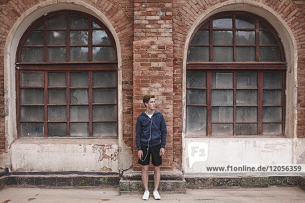 Junger Mann mit Kopfhörern im Backsteingebäude schaut sich um