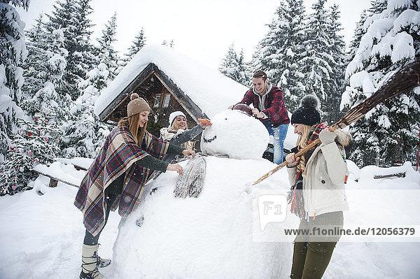 Österreich  Altenmarkt-Zauchensee  Freunde bauen großen Schneemann am Holzhaus auf