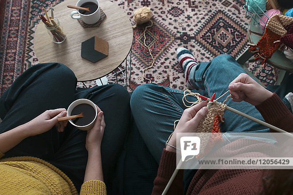Young couple knitting and having cup of coffee in living room  top view