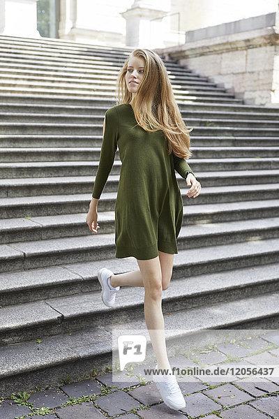Porträt einer jungen Frau in grünem Kleid  die die Treppe hinuntergeht.