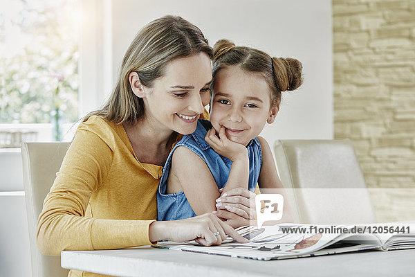 Glückliche Mutter mit Tochter zu Hause beim Betrachten des Bilderbuches