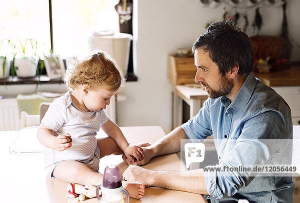 Vater spielt mit dem kleinen Jungen  der auf dem Küchentisch sitzt.