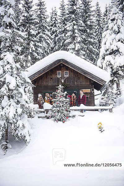 Österreich  Altenmarkt-Zauchensee  Freunde schmücken Weihnachtsbaum im Holzhaus