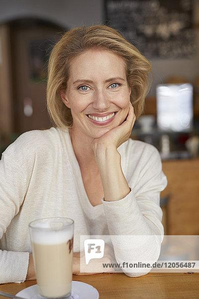 Porträt einer entspannten Frau mit Latte Macchiato im Café