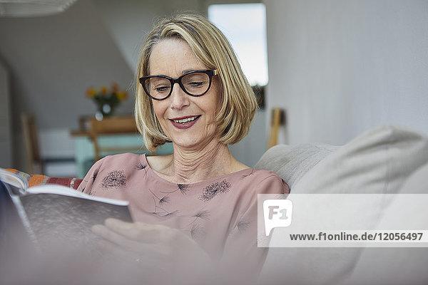 Lächelnde reife Frau zu Hause auf dem Sofa beim Lesen eines Buches
