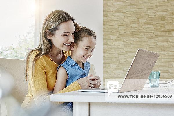 Glückliche Mutter mit Tochter zu Hause auf dem Laptop