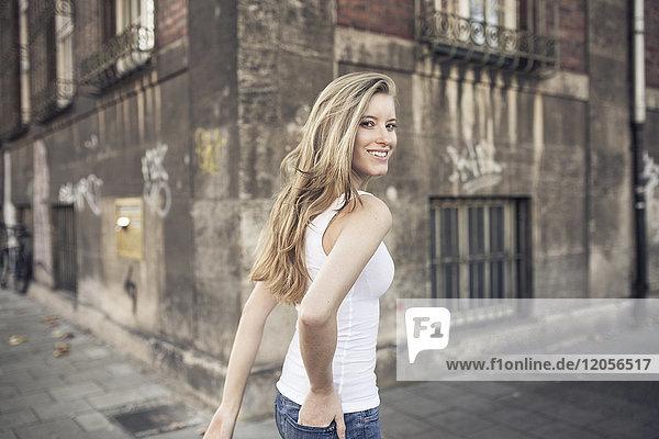 Porträt einer lächelnden jungen Frau beim Spaziergang