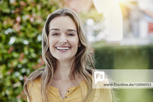Porträt einer glücklichen Frau im Garten