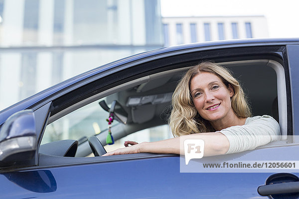 Porträt einer lächelnden Frau im Auto