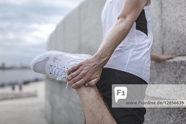 Nahaufnahme des Athleten beim Stretching im Freien