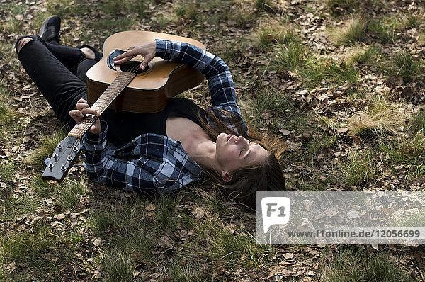 Frau auf der Wiese liegend  Gitarre spielend