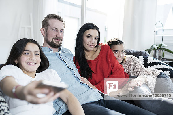 Parents and twin daughters on sofa in living room watching Tv