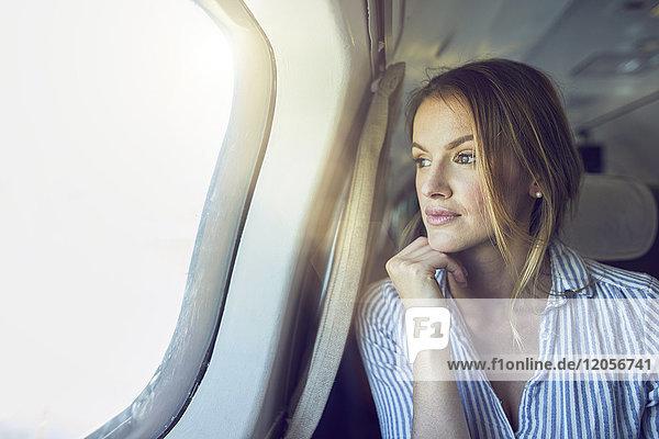 Ernsthafte Frau schaut aus dem Flugzeugfenster