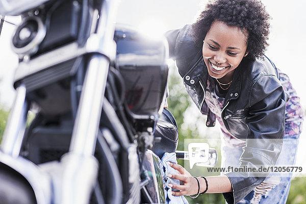 Junge Frau reinigt ihr Motorrad