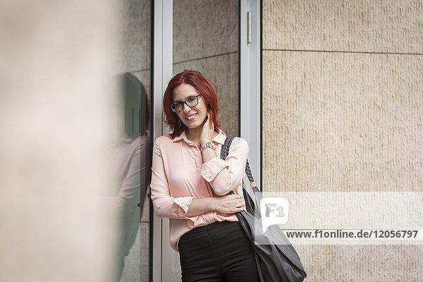Junge Geschäftsfrau  die sich gegen die Glasscheibe lehnt  lächelnd