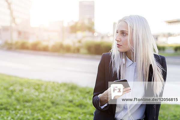 Young businesswoman in the city with cell phone and earphones looking around