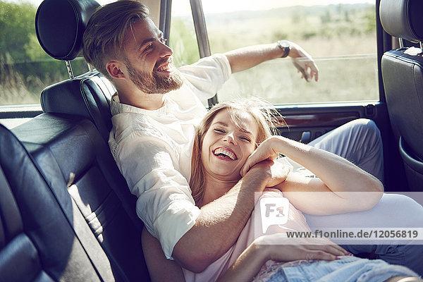 Glückliches junges Paar entspannt im Auto